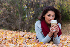 Hispanic woman enjoying a coffee outdoors during fall Royalty Free Stock Photography