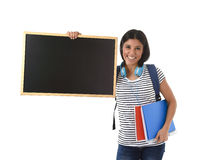 Hispanic woman or female student holding blank blackboard with copy space for adding message. Young beautiful hispanic woman or female student holding blank Stock Images