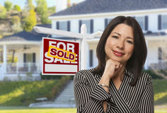 Hispanic Woman in Front of Sold Sign and House Stock Photo