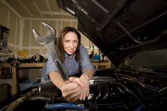Hispanic woman in garage with wrench. Pretty Hispanic woman with wrench working on car in garage royalty free stock photography