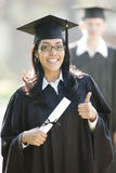 Hispanic Woman Graduate. Latin woman graduate with thumbs up in graduation cap and gown and diploma Stock Photography