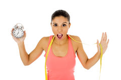 Hispanic woman holding alarm clock and taylor measure tape in time for sport and diet concept Stock Photos