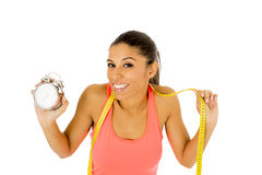 Hispanic woman holding alarm clock and taylor measure tape in time for sport and diet concept Stock Image