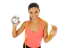 Hispanic woman holding alarm clock and taylor measure tape in time for sport and diet concept Stock Photo