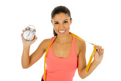 Hispanic woman holding alarm clock and taylor measure tape in time for sport and diet concept Royalty Free Stock Images