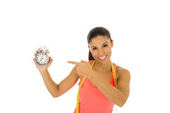 Hispanic woman holding alarm clock and taylor measure tape in time for sport and diet concept Royalty Free Stock Photos