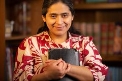 Hispanic Woman Holding Bible and Looking Directly at the Camera. With Background of Bookshelf royalty free stock photo
