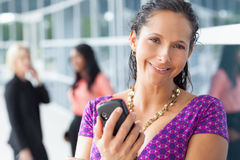 Hispanic woman holding cell phone Royalty Free Stock Image