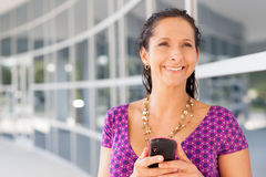 Hispanic woman holding cell phone Royalty Free Stock Photo