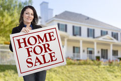 Hispanic Woman Holding Home For Sale Sign in Front of House Royalty Free Stock Photos