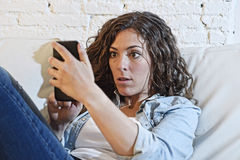 Hispanic woman holding mobile phone in crazy eyes social network and internet addiction concept. Young hispanic woman holding mobile phone looking in crazy eyes stock photo
