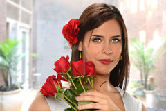 Hispanic Woman Holding Red Roses Stock Photo