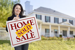Hispanic Woman Holding Sold Home Sale Sign in Front of House Stock Photography