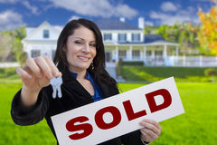 Hispanic Woman Holding Sold Sign and Keys In Front of House. Hispanic Woman Holding Sold Sign and Keys In Front of Beautiful House Stock Image