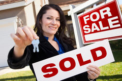 Hispanic Woman Holding Sold Sign and Keys, House. Happy Attractive Hispanic Woman Holding Sold Real Estate Sign and Keys in Front of For Sale Real Estate Sign Royalty Free Stock Images