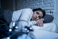 Hispanic woman at home bedroom lying in bed late at night trying to sleep suffering insomnia. Young beautiful hispanic woman at home bedroom lying in bed late at stock photography