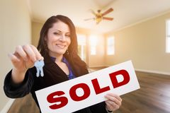Hispanic Woman With House Keys and Sold Real Estate Sign In Empty Room of House. Hispanic Woman With House Keys and Sold Real Estate Sign In Empty Room of a New royalty free stock photo