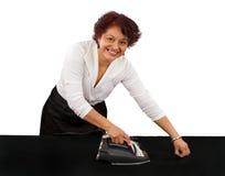 Hispanic Woman Ironing Sheet royalty free stock photos