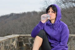Hispanic woman jogging - water break Royalty Free Stock Image