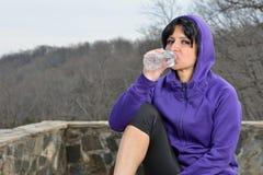 Hispanic woman jogging - water break Royalty Free Stock Image