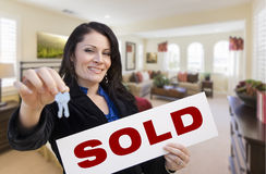Hispanic Woman with Keys and Sold Sign in Living Room. Happy Hispanic Woman with House Keys and Sold Sign in Beautiful Living Room Royalty Free Stock Photos