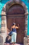 Hispanic woman knocking on door Stock Photo