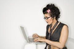 Hispanic woman on laptop. Royalty Free Stock Images