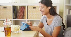 Hispanic woman laughing and using tablet on coffee table Stock Photo