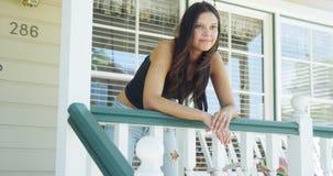 Hispanic woman leaning on rail smiling Royalty Free Stock Images