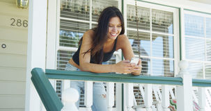Hispanic woman leaning on rail texting Royalty Free Stock Images
