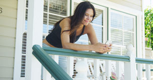 Hispanic woman leaning on rail texting Stock Photography