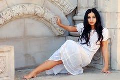 Hispanic woman leaning on a stone wall Stock Photo
