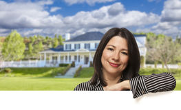Hispanic Woman Leaning on White in Front of House Stock Photo