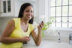 Hispanic woman listening to music on mp3 player Royalty Free Stock Photos