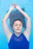 hispanic woman with long black  hair, floating back in the blue swimming pool Stock Images
