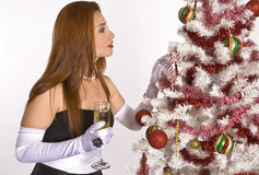 Hispanic woman looking at a decorated Christmas Tree. A Hispanic woman in an evening gown and white gloves, holding a drink, while looking at a decorated Stock Image
