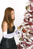 Hispanic woman looking at a decorated Christmas Tree. A Hispanic woman in an evening gown and white gloves, holding a drink, while looking at a decorated Stock Photography