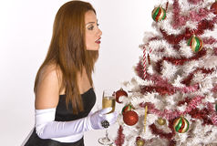 Hispanic woman looking at a decorated Christmas Tree. A Hispanic woman in an evening gown and white gloves, holding a drink, while looking at a decorated Royalty Free Stock Photography