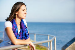 Hispanic Woman Looking Over Railing At Sea Royalty Free Stock Images