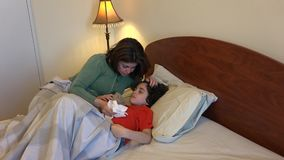Hispanic woman looking after sick son stock video