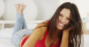 Hispanic woman lying on bed smiling Royalty Free Stock Photography