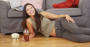 Hispanic woman lying on living room floor with iced tea Royalty Free Stock Photo