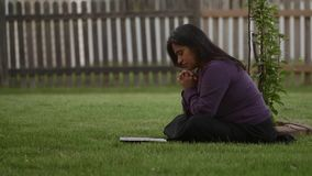Hispanic Woman Meditates During Worship Time. In Back Yard at home stock footage