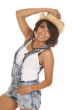 Hispanic woman overalls hand on hat and in pocket Stock Photo