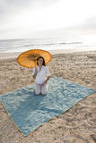 Hispanic woman with parasol on beach blanket Stock Photo
