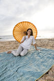 Hispanic woman with parasol on beach blanket Stock Images