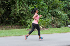 Hispanic woman in pink jogging at outdoor park Royalty Free Stock Photography