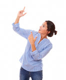 Hispanic woman pointing up her arms Royalty Free Stock Photos