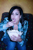 Hispanic woman with popcorn watching television royalty free stock image