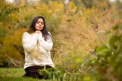 Woman Praying in Forest Preserve Alone During a Beautiful Autumn Day stock photo
